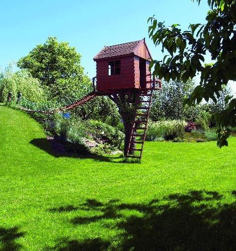 Mała architektura - domek na pniu jabłoni, mostek linowy i stok sztucznego pagórka są miejscami zabawy dla dzieci przez cały rok