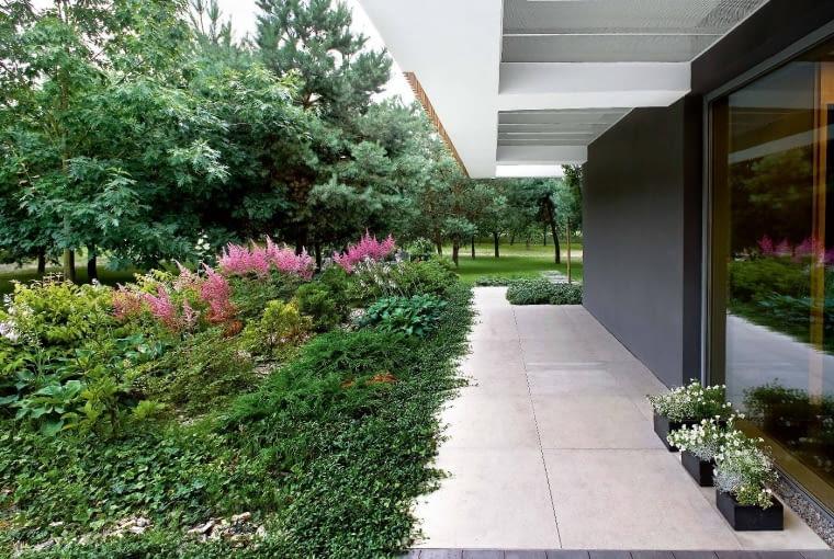 Prosta, ale ekspresyjna architektura harmonizuje zkrajobrazem. Drewniane elementy na elewacjach dodają budynkowi lekkości. Malowniczą zieleń wotoczeniu domu zaprojektowała pracownia K+ Krajobraz Dodany.
