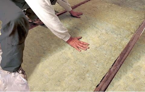 Układanie wełny mineralnej na stropie drewnianym - po ułożeniu folii paroszczelnej, między drewnianymi elementami konstrukcyjnymi stropu umieszcza się pasy izolacji cieplnej. Powinny być one przycięte na szerokość o około 2 cm większą niż rozstaw belek