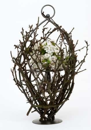 Metalowy stelaż szklanego naczynia ukryto między gałązkami wiśni. Do środka wstawiono kwitnące pędy ułożone w kulę.
