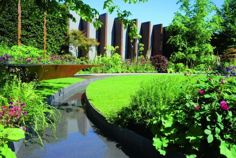 Trawnik i woda to wyróżniki tego nowoczesnego ogrodu. Mógłby wydawać się zbyt surowy i sterylny, gdyby nie naturalistyczne rabaty. Ciekawym elementem ogrodzenia jest żywa zielona ściana (z lewej).