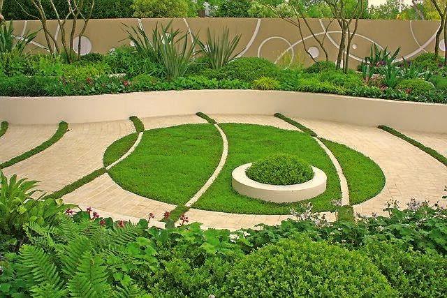 Pomiędzy betonowymi kostkami 'namalowano' zielone pasy z trawy. Natomiast na murawie - białe łuki z kostki. Przy takim rozwiązaniu trzeba wybrać nasiona traw odpornych na deptanie, a skrawki murawy - regularnie podlewać i kosić.