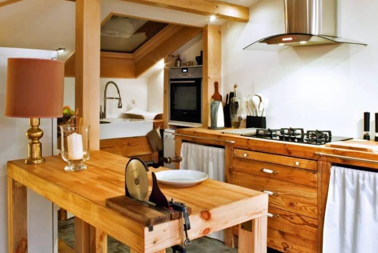 Kuchnie. Oryginalne szafki i stół, który jest dodatkowym blatem roboczym, zbudował samodzielnie pan domu - nie jest stolarzem, ale z drewna potrafi zrobić niemal wszystko. Jako materiał posłużyły mu modrzewiowe belki pozyskane podczas przebudowy dachu. Blat jest z litego buku. Po zaolejowaniu różne barwy tych dwóch gatunków drewna się wyrównały.