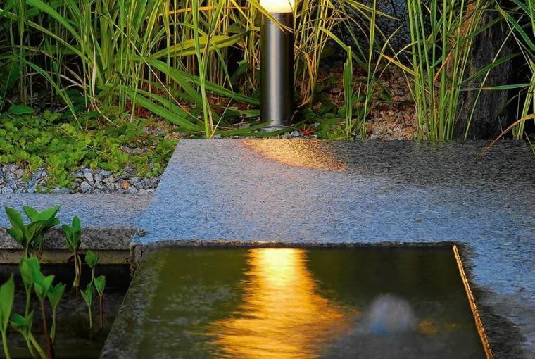 LAMPA umieszczona nad brzegiem oczka odbija się w wodzie, a jej światło pięknie rozmywa się w pomarańczową nieregularną plamę