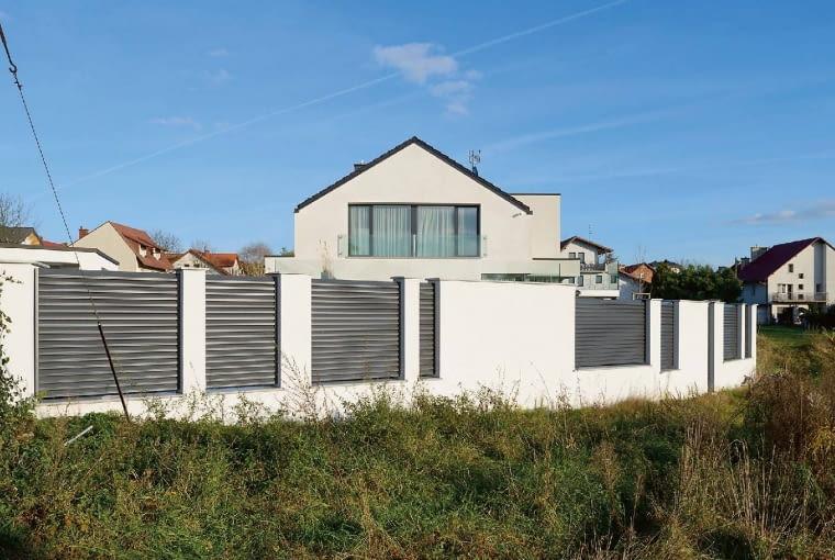 Swoim wyglądem ogrodzenie nawiązuje do materiałów i kolorystyki domu, a przy okazji spełnia też ważną funkcję, o której często zapomina się, gdy kupujemy działkę otwartą z jednej strony na malownicze pola - jak tutaj. Pamiętajmy, że jest niemal pewne, iż ich miejsce zajmą kolejne ciasno ulokowane domy...