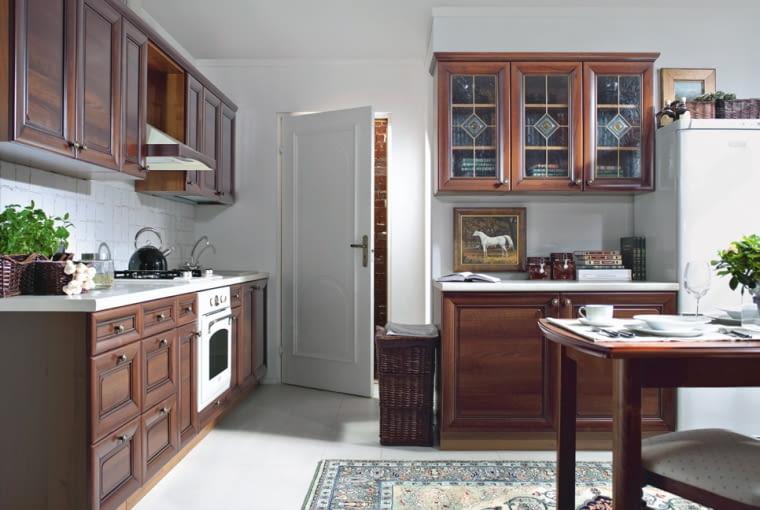 Tylko dostojne brązy i kremowe biele. Gzyms wykańczający szafki od góry oraz ozdobne przeszklenia nawiązują do dawnych wzorów. Zdjęcie: Black Red White