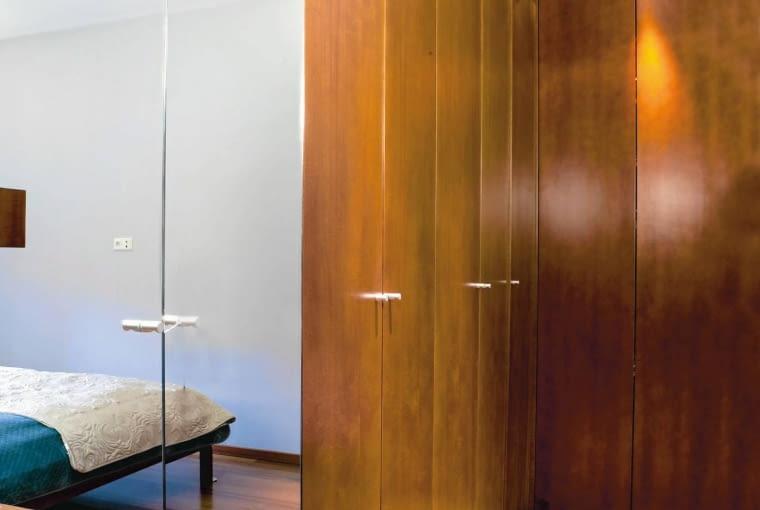 W sypialni nie mogło zabraknąć dużego lustra, w którym można się przejrzeć od stóp do głów. Na ścianach nie było już na nie miejsca, szklanymi taflami pokryto więc dwa fronty szafy. Chwile spędzone na szykowaniu się do wyjścia umila muzyka płynąca z głośników zamontowanych w podwieszonym suficie.