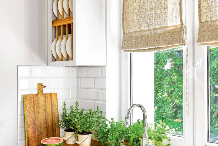 SZAFKI zpłycinami idużymi metalowymi uchwytami nawiązują do stylu kuchni sprzed lat. Rolety (podobnie jak zasłony do sypialni) uszyto wLnianym Zaułku.