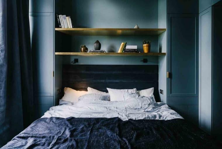 Z kolei sypialnia tonuje nastroje, by móc się wyciszyć po dniu pracy i nastroić na dobry sen. Zaaranżowano ją w nieco buduarowym stylu: ściany wraz z zabudową pokryte są farbą w kolorze szaro-niebieskim, ocieplone mosiężnymi półkami. Jest miękko i nastrojowo.