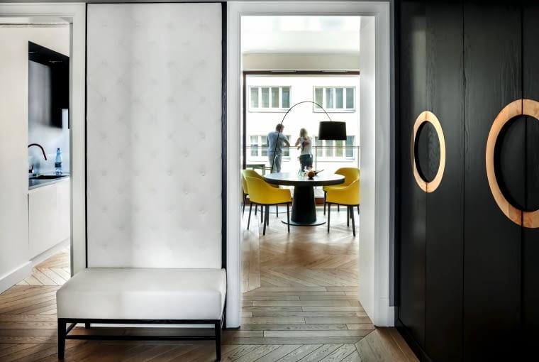 Apartament ma otwarty układ i doskonałą ekspozycję słoneczną. Podział funkcji wytyczają kurtynowe ścianki i układ klepek. Na pierwszym planie tapicerowana ławka i szafa fornirowana hebanem - obie wykonane na zamówienie (ADM Meble Dariusz Głogoski).