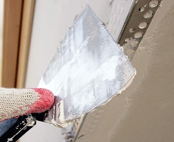 Krok 12. Naroże obudowy wzmacnia się metalowym kątownikiem, wtapiając go w masę szpachlową. Po jej wyschnięciu nakłada się gładź gipsową.