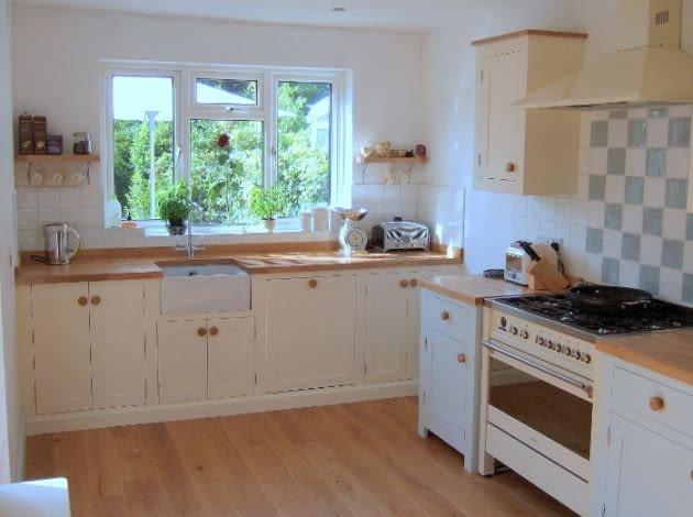 Widok na kuchnię z pralką z poprzedniego zdjęcia - po zamknięciu drzwiczek trudno domyśleć się gdzie jest pralka.