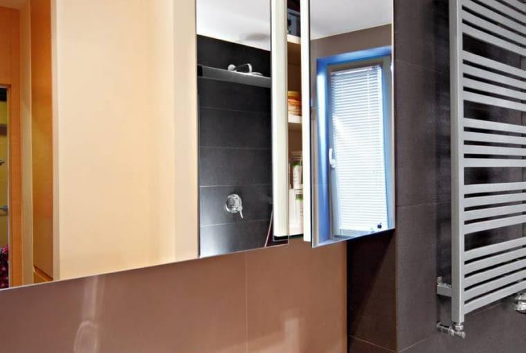 Nad umywalką zbudowano szafkę z lustrzanym frontem, przeznaczoną na kosmetyki. Dwie pozostałe tafle to już klasyczne lustra; na jednym z nich zainstalowano kinkiet w kształcie prostopadłościanu, oświetlający strefę umywalkową.