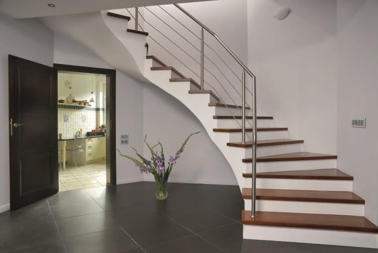 DOM. Biało-grafitowy hol wygląda bardzo nowocześnie. Takie też musiały być schody. Wybrano drewniane stopnie z metalową balustradą.