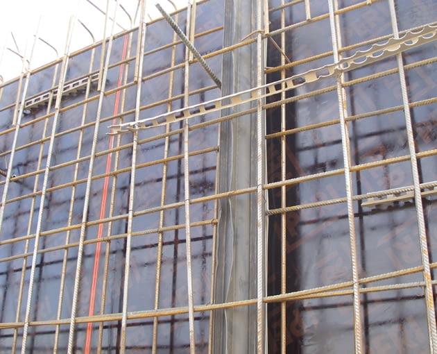 Wewnętrzna ściana piwnic. Zbrojenie powierzchniowe ściany jest wyprowadzone powyżej deskowania; będzie później połączone ze zbrojeniem stropu piwnicy. Widoczna pośrodku rura uszczelniająca z PVC została umieszczona w miejscu przerwy roboczej podczas betonowania ścian (gwarantuje jej szczelność)
