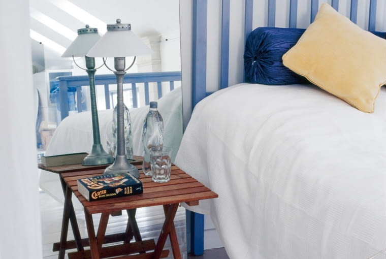 xGlass+metal lamp on small table in front of mirror beside blue painted bed with yellow velvet cushion and white bedcover