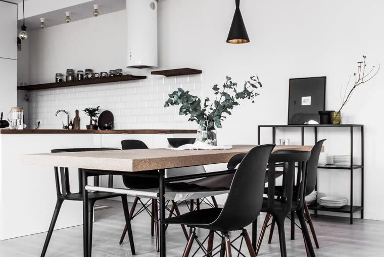 Prosty stół przybrany zestawem różnych krzeseł jest na tyle duży, że z powodzeniem zmieści rodzinę i gości. Jego lekki blat wykonano z korka (seria Sinnerlig). Nad nim blikują czarno-złote lampy z kolekcji Pedro.