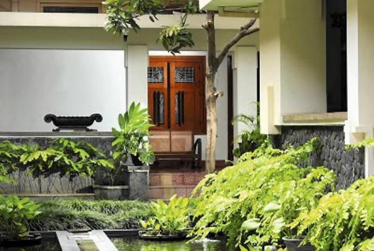 Betonowe kładki przerzucone nad wodą prowadzą do domu i na taras - kolorem współgrają z elewacją budynki