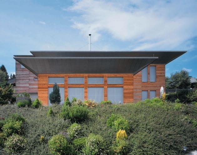 Przy fikuśnych eksperymentach z bryłą warto wykończyć dom z użyciem prostych materiałów, np. blachy i drewna tak, a by nie konkurowały z formą budynku.