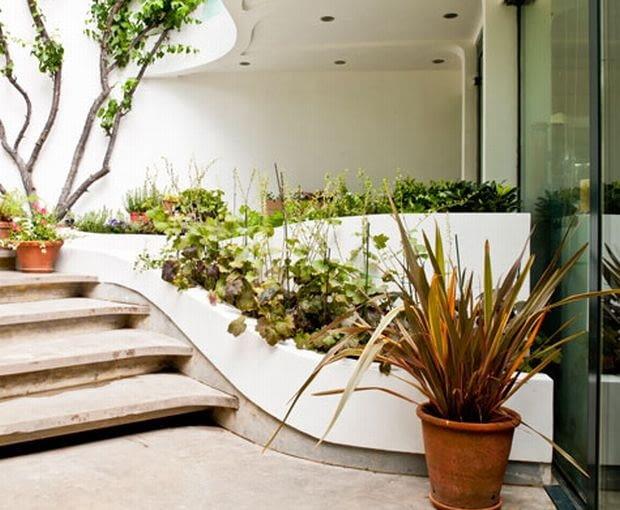 Płynne, wijące się formy przenikają z ogrodu do wnętrza Clapham House.