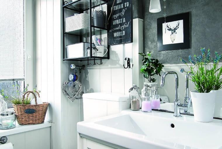 Niewielką łazienkę urządzono jak salonik kąpielowy - znalazło się tu miejsce nawet na rośliny doniczkowe i obrazki. Drewniane panele na ścianie pomalowano farbą odporną na wilgoć, wyżej położono tynk imitujący beton.