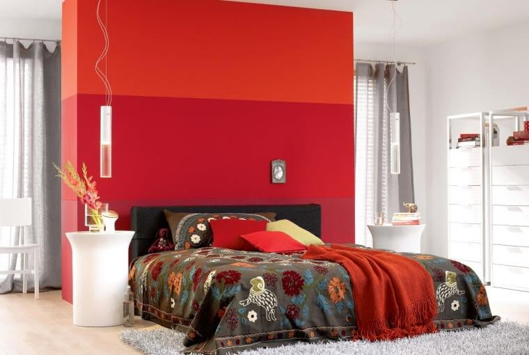 Wbrew pozorom czerwień dobrze wygląda w towarzystwie pokrewnych odcieni: różu i pomarańczu. Tutaj trzy różne pasy stworzyły oryginalne tło łóżka. Uwaga: gdy we wnętrzu dominuje ognisty kolor, warto zadbać o dobre oświetlenie - tylko wtedy stworzy on ciepłą i przytulną atmosferę.