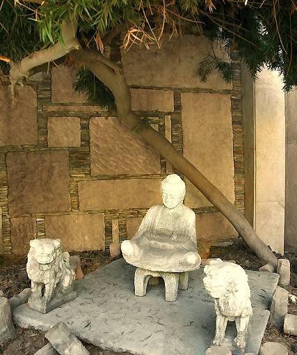 Stylowa kamienna rzeźba to detal chętnie stosowany przez projektantów orientalnych ogrodów.
