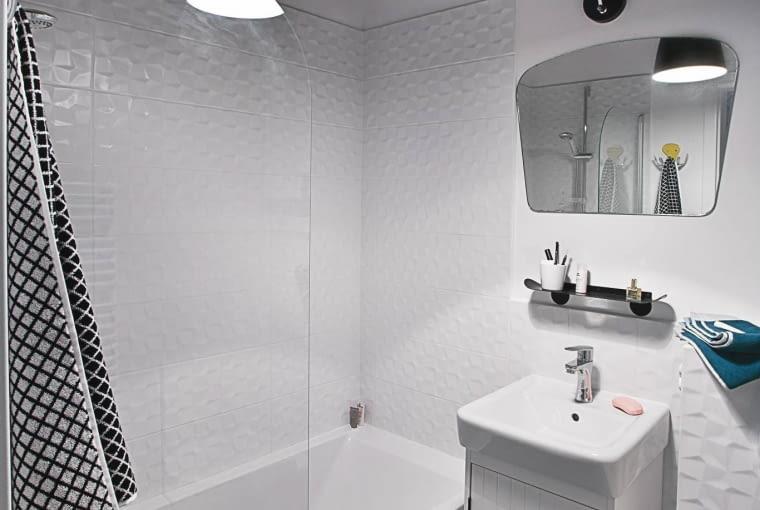 W MAŁEJ ŁAZIENCE najlepiej sprawdza się wanna z parawanem. Lustro z lat sześćdziesiątych (po poprzedniej właścicielce) projektantki wyciągnęły z piwnicy. W prostej szafce z IKEA zamontowano oryginalny uchwyt, który jest zarazem wieszakiem na ręcznik.