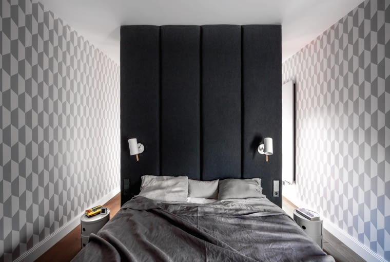 Sypialnię projektantki urządziły nietypowo, lokując łóżko tyłem do okna i separując je od jasnej części pokoju tapicerowaną ścianką. To podzieliło wnętrze na część nocną i dzienną - za ścianką mieści się garderoba.