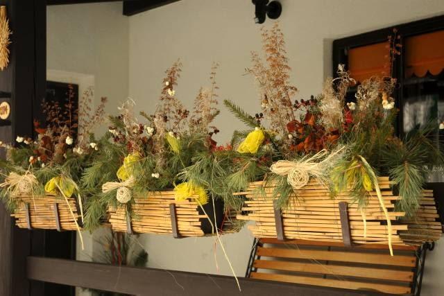 Z balkonowych skrzynek mogą 'wyrastać' ozdobione sizalowymi kokardkami suche kwiatostany polnych roślin oraz gałęzie sosny, świerka i śnieguliczki.