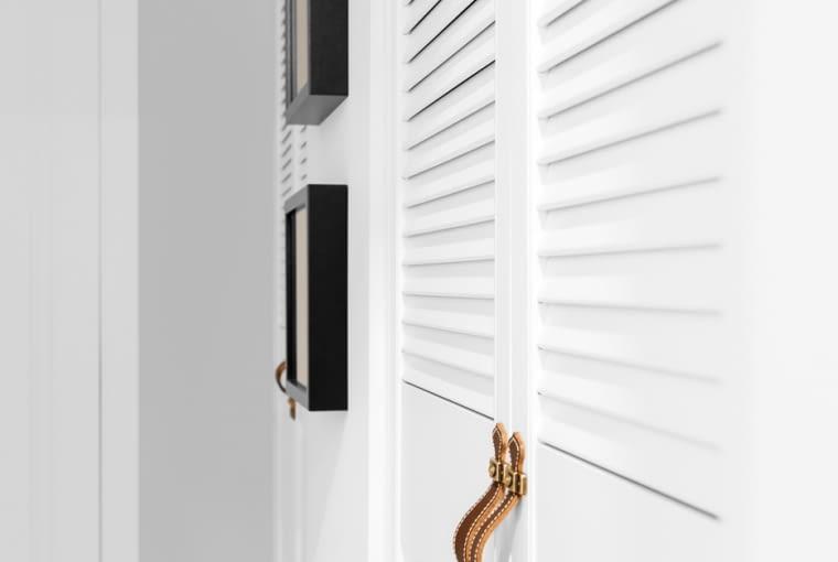 Idąc holem w głąb mieszkania mijamy szafy z ażurowymi drzwiami, których design nawiązuje do stylu hampton.