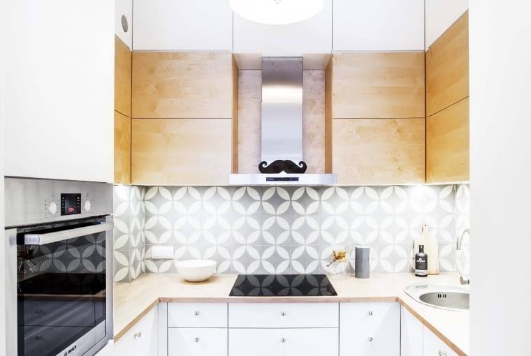 W NAWIĄZANIU. W prostej białej kuchni część frontów zrobiono ze sklejki, idealnie pasującej do drewnianego blatu.