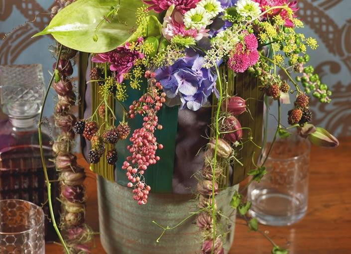 Orientalne kompozycje kwiatowe. Brzegi wazonu zdobią szerokie wstążki. Spływają na nie pędy owocujących jeżyn, owocostany przestępu i czarnuszki, pędy winnika. Czaszę bukietu tworzą anturium, koper, dalie, horensje, chryzantemy, kwiatostany szkarłatki i liście żurawki