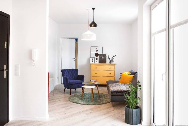 Z ZASKOCZENIA: ten widok pokoju dziennego nie zapowiada jeszcze feerii kolorów. Chyba że zajrzymy za ściankę, na której wisi domofon (po drugiej stronie stoi czerwona szafka). Albo uchylimy drzwi do sypialni pomalowanej na kobaltowy kolor.