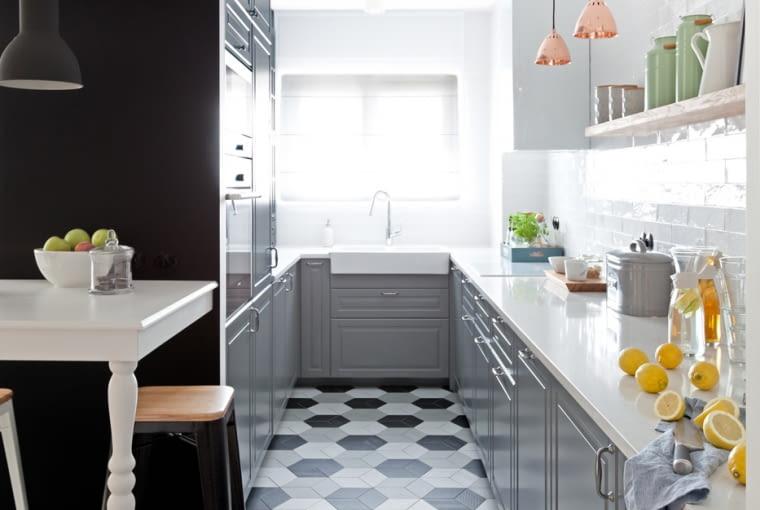 Pomimo, że kuchnia jest wąska, zdecydowano się jej nie otwierać całkowicie na salon. Maksymalnie rozplanowane szafki w kształcie litery C zapewniają funkcjonalność jej użytkowania. Na podłodze płytki ułożone w przepiękny heksagonalny deseń.