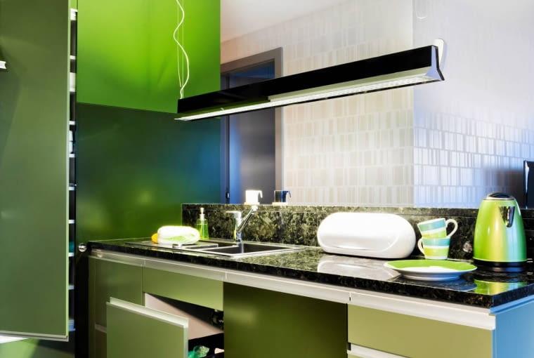PRZECHOWYWANIE W KUCHNI. Do barwy frontów idealnie dobrano kuchenne blaty z zielono-szarego granitu. Struktura kamienia przypomina rybie łuski, które połyskują w świetle lamp i dają efekt trójwymiarowości. Nad półwyspem -wzorowana na fabrycznym oświetleniu lampa Factory marki Fabbian.