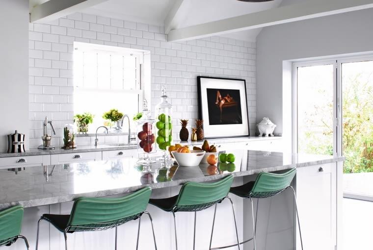 W kuchni odsłonięto więźbę dachową, aby nadać wnętrzu loftowy charakter, który podkreślają też cylindryczne lampy. Stołki przy imponującym marmurowym blacie znalezione na eBayu.