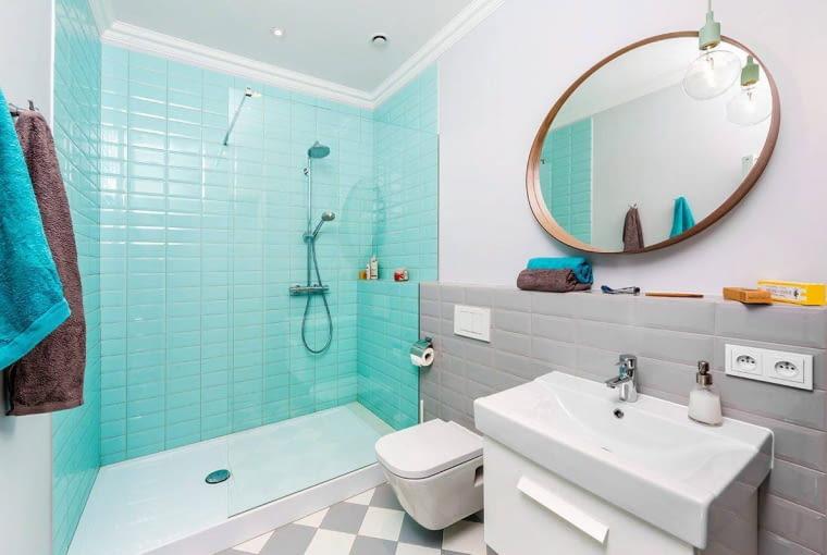 Odmienna kolorystyka dzieli umownie łazienkę na strefy: kąpielową, z kabiną prysznicową zbudowaną wzdłuż całej krótszej ściany, oraz toaletową - z sedesem i umywalką na szafce.