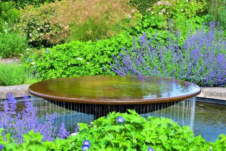 Stylowej fontannie uroku dodają niebieskie bodziszki i kocimiętki.