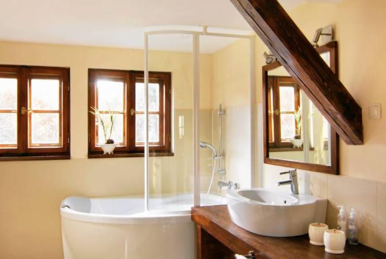 DOM. Belka konstrukcyjna wpisuje się wwystrój nowoczesnej łazienki. Doniej nawiązuje wykonany zdrewna dębu gruby blat pod umywalkę orazdębowa wstawka w podłodze, przywołująca na myśl chodnik.