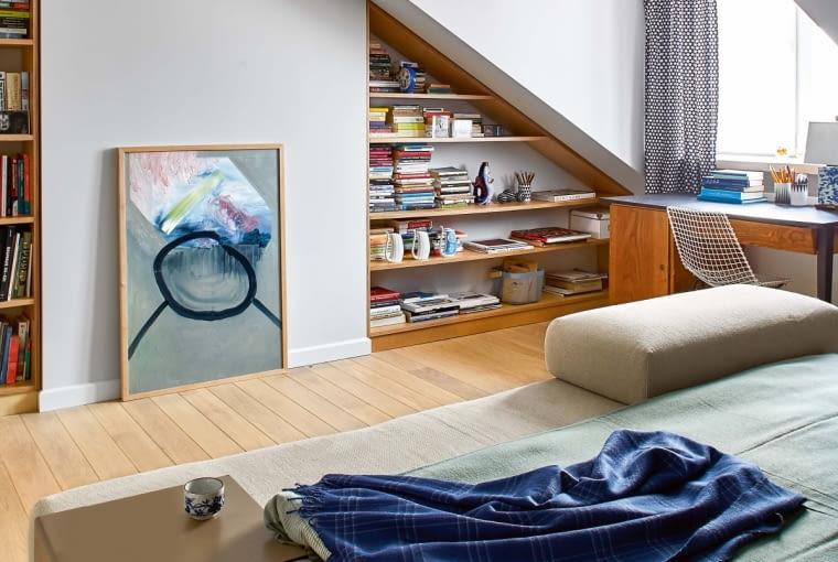 Domowe biuro usadowiło się w sypialni przy oknie. Modernistyczne biurko to prezent od przyjaciela. Towarzyszy mu współczesna replika krzesła ogrodowego z lat sześćdziesiątych XX wieku, projektu Henryka Sztaby (wyprodukowana przez Mamsam). Wnękę pod skosem zajęła biblioteczka. Obraz namalowała Dorota Buczkowska.