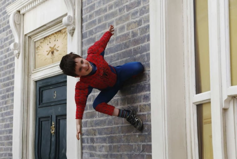 "Dressed as Spiderman, Alfie Morrison, 4, is reflected as he poses on Argentine artist Leonardo Erlich's optical illusion installation ""Dalston House"" in east London June 26, 2013. The artwork, commissioned by the Barbican Gallery, uses mirrors to create the impression of a house on which people can play and pose for visual effect. REUTERS/Luke MacGregor (BRITAIN - Tags: ENTERTAINMENT SOCIETY)"