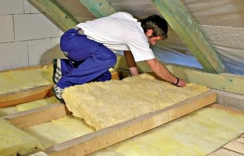 Układanie wełny mineralnej na stropie drewnianym - między belkami układa się drugą warstwę wełny mineralnej. Choć nie jest to konieczne, od góry można ją dodatkowo zabezpieczyć wysokoparoprzepuszczalną folią dachową (membraną dachową)