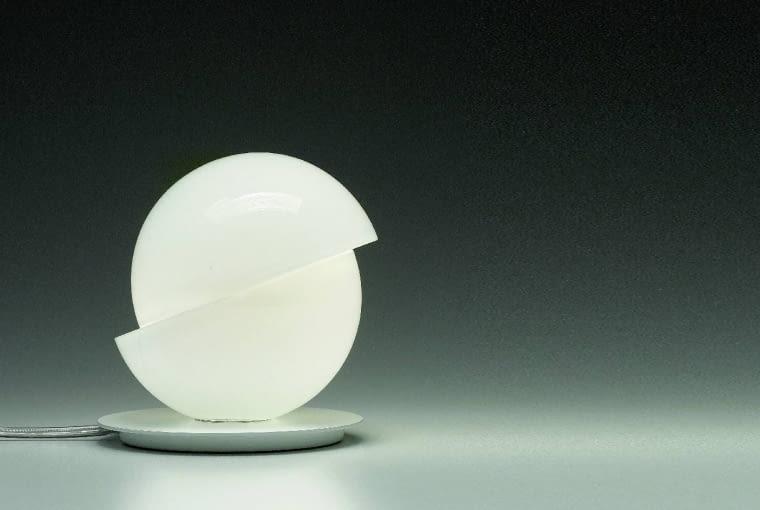 Aibu: Niewielka lampa stołowa w kształcie kuli pękniętej na pół. Zrobiona z super wytrzymałego szkła typu triplex, na podstawie ze zmatowionego metalu. Dwie zachodzące na siebie półkule tworzą iluzję ruchu. Ledy zamknięte wewnątrz klosza dają kameralne, nastrojowe światło. 920 zł, Axo Light, axolight.it/lafaktoria.pl