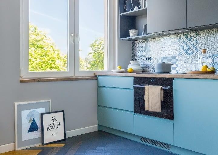 Nie ma monotonii. Różne odcienie niebieskiego wprowadzają powiew świeżości do aneksu kuchennego. Atmosferę dodatkowo ożywia zestawienie ze sobą w jednej strefie różnych faktur i form. Otwarte półki w górnym rzędzie szafek dodają lekkości zabudowie.