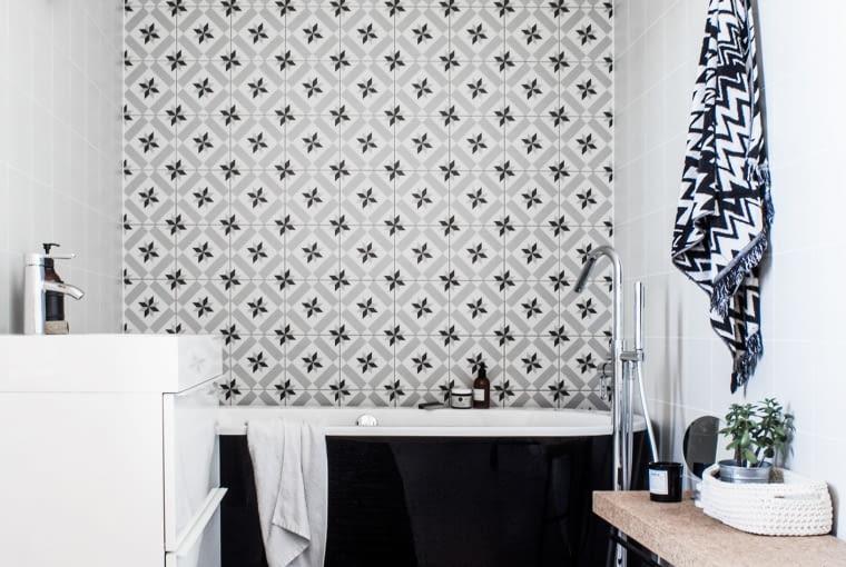 Druga łazienka ma charakter pokoju kąpielowego z wolnostojącą czarną wanną umieszczoną na tle kafli o intensywnym wzorze.