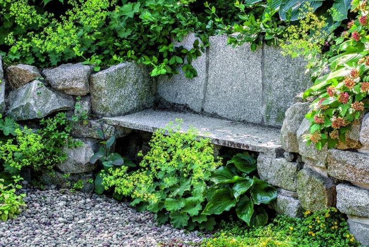 Kamienna ławeczka otulona przywrotnikiem to niebanalna ozdoba niewielkiego wgłębnika.