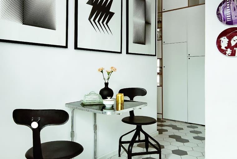W kuchni dalsza część ekspozycji sztuki: talerze z polskich manufaktur (lata 60.) oraz graficzny tryptyk autorstwa Leszka Hołdanowicza. Industrialne francuskie krzesła, które kolorem i linią współgrają z grafikami na ścianie. Złoty mlecznik Tom Dixon (Nap).