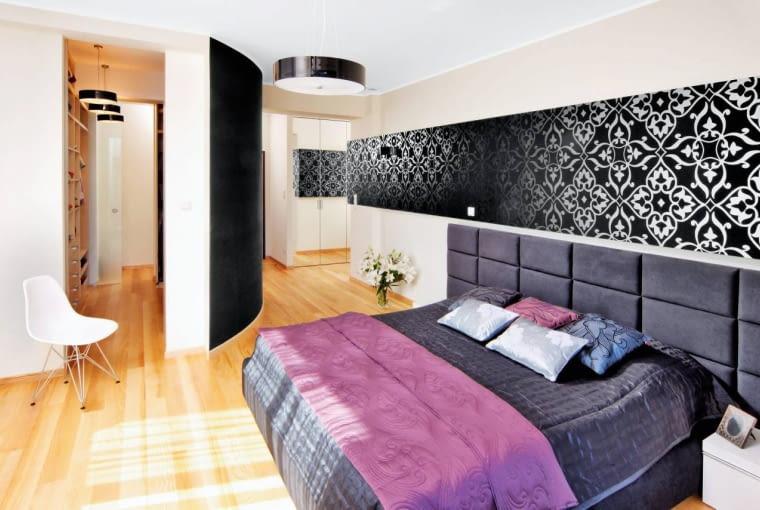 Właścicielom mieszkania zależało na tym, by większość schowków na ubrania znalazła się w przestronnej sypialni (około 25 m kw.), bo wtedy nie musieliby zagracać masywnymi szafami pokoju dziennego. Projektantka zaproponowała popularne ostatnio rozwiązanie - wydzielenie w sypialni osobnej garderoby. Nowe pomieszczenie ma powierzchnię mniej więcej 6 m kw. Jego boczną ściankę zbudowano z płyty gipsowo-kartonowej wygiętej w łuk. Ten nietypowy kształt został wybrany głównie ze względów praktycznych - łukowata przegroda nie przytłacza pokoju tak jak ściana załamująca się pod kątem prostym, poza tym ułatwia bezpieczne poruszanie się po sypialni (na jej środku jest więcej miejsca). Po obydwu stronach pojemnej garderoby znajdują się głębokie, 60-centymetrowe półki oraz liczne wieszaki i szuflady. Mimo że mieści się tutaj bardzo dużo ubrań, postanowiono zbudować jeszcze dodatkowe schowki. W korytarzyku prowadzącym z sypialni do łazienki powstała więc szafa długości trzech metrów, sięgająca od podłogi aż do sufitu. Gospodarze zdecydowali się na lustrzane fronty, które optycznie powiększają i rozświetlają to wąskie przejście, a przy okazji zastępują duże lustro ścienne, niezbędne podczas ubierania się.