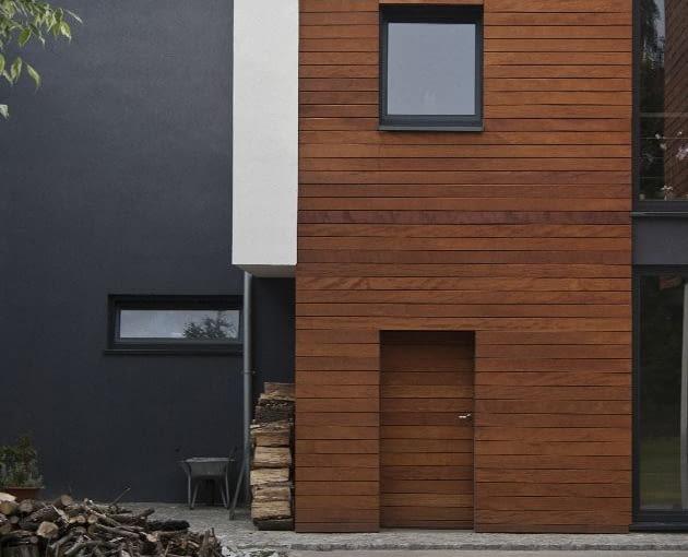 """W wyłożonej drewnem elewacji """"schowano"""" drzwi do pomieszczenia na sprzęt ogrodowy"""